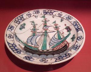 Plat à décor de barques aux trois grandes voiles rayées, Iznik, Turquie, vers 1700. Céramique siliceuse à décor peint sous glaçure transparente.